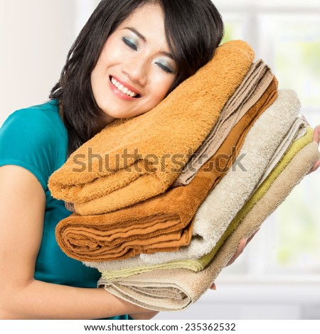 woman doing a housework holding laundry. smell good - stock photo