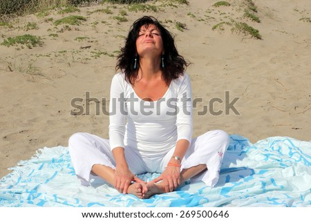 woman doing a sitting position on a shore - stock photo