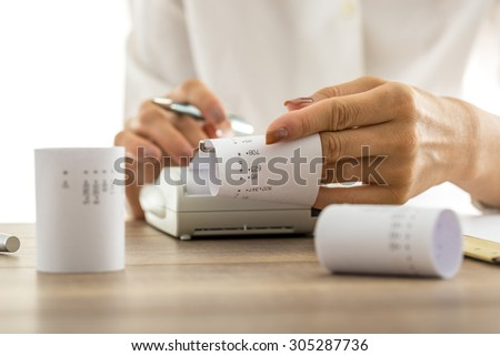 Woman doing calculations on an adding machine or calculator pulling off reams of paper with printed figures and totals, conceptual of accounting a bookkeeping, close up of her hands. - stock photo