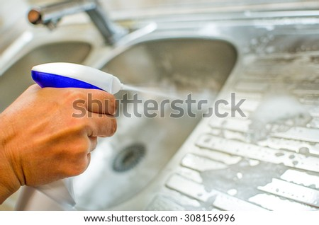 Woman doing chores in the kitchen at home , sink and faucet with multipurpose - stock photo