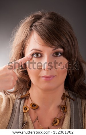 Woman doing EFT on the corner of the eye point. Emotional Freedom Techniques, tapping, a form of counseling intervention that draws on various theories of alternative medicine. - stock photo