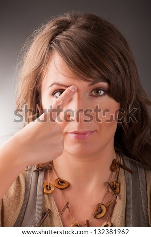 Woman doing EFT on the end of eyebrow point. Emotional Freedom Techniques, tapping, a form of counseling intervention that draws on various theories of alternative medicine. - stock photo