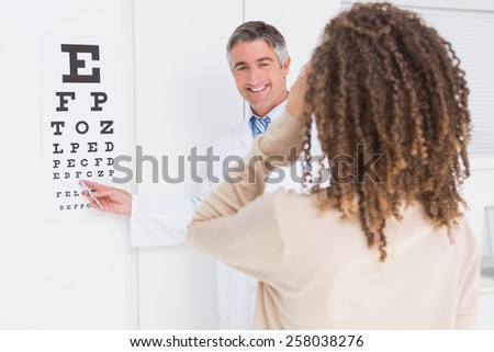 Woman doing eye test with optometrist in medical office - stock photo