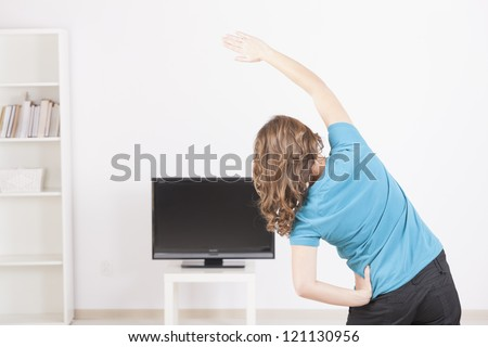 Woman doing fitness at home using on screen TV instructions - stock photo