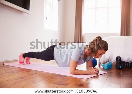 Woman Doing Fitness Exercises On Mat In Bedroom - stock photo