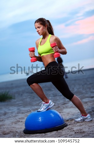 Woman doing fitness exercises with bosu ball on the beach - stock photo