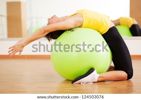 Woman doing fitness in a gym on a ball - stock photo