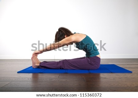 woman doing gymnastics on mat over white background - stock photo