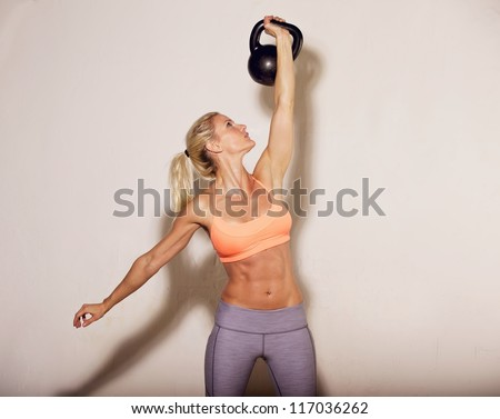 Woman doing her kettlebell workout - stock photo