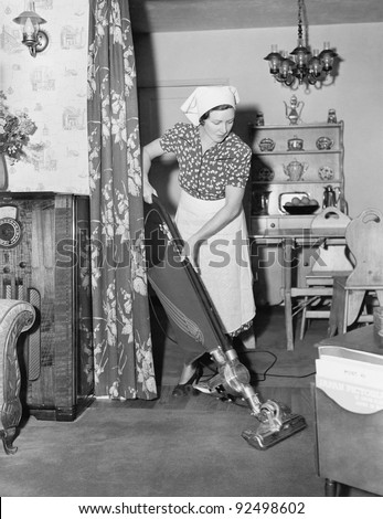 Woman doing housework with a vacuum cleaner - stock photo