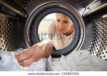 Woman Doing Laundry Reaching Inside Washing Machine - stock photo