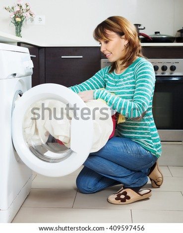 woman doing laundry with washing machine at home kitchen