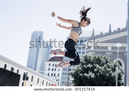 Woman doing parkour in the city on a sunny day - stock photo