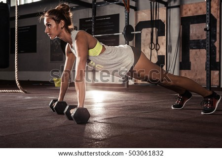 Woman doing push-up exercise with dumbbell. Strong female doing workout.