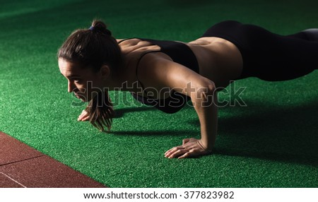Woman doing push-up in gym - stock photo
