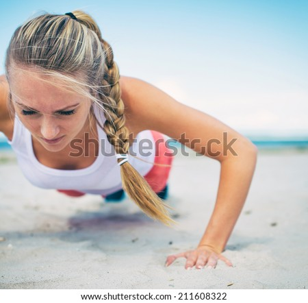 Woman doing push-ups on the beach. - stock photo