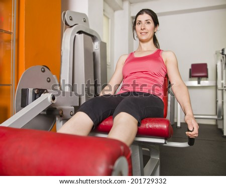 Woman doing quadriceps exercises on gym machine - stock photo