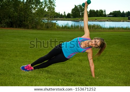 Woman doing side planks with dumbbells in a park.