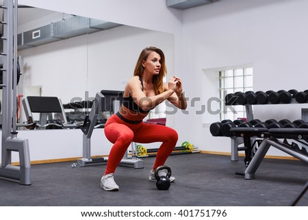 Woman doing squat exercise at gym - stock photo