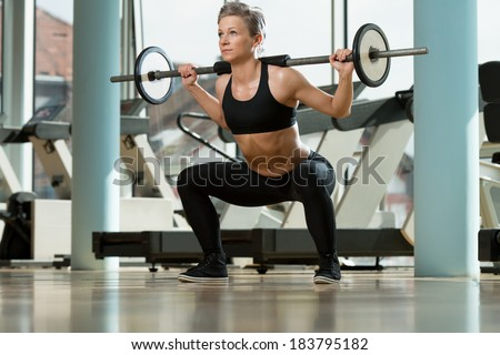 Woman Doing Squats - Beautiful Fit Female Doing Barbell Squats In The Gym - stock photo
