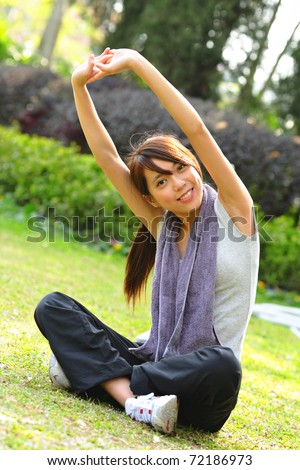 woman doing stretching exercise in park - stock photo