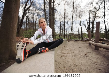 Woman doing stretching exercise in park. Caucasian female model exercising in nature. - stock photo