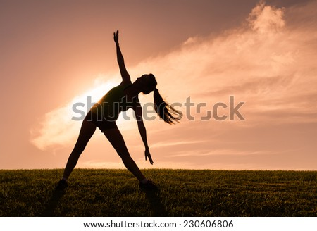 Woman doing stretching exercise outdoors - stock photo