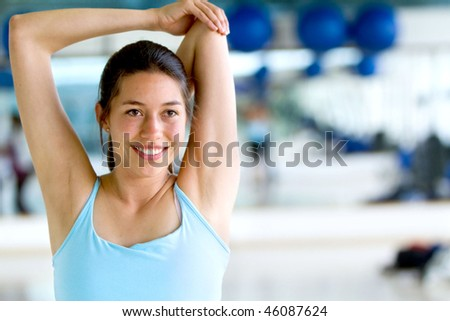 Woman doing stretching exercises for her arm and back at the gym - stock photo