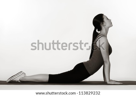 woman doing stretching exercises on a mat shot in the studio - stock photo