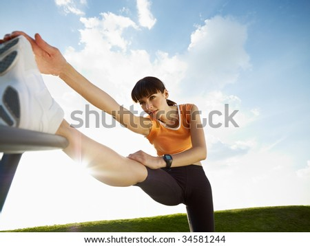 woman doing stretching outdoors at sunset. Low angle view, copy space - stock photo