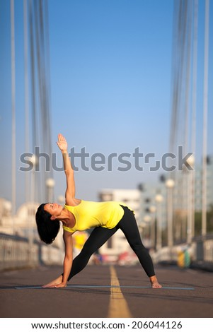 Woman doing stretching yoga exercises outdoors on the bridge - stock photo