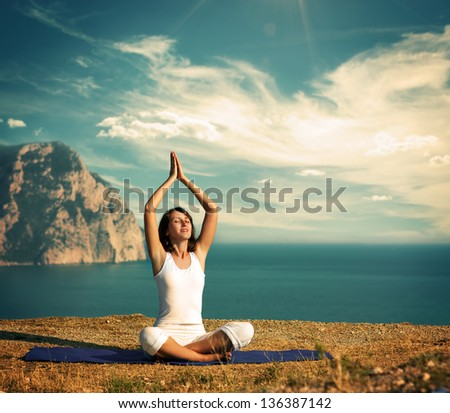 Woman Doing Yoga at the Sea and Mountains - stock photo