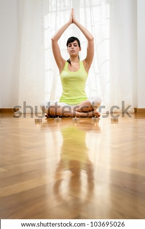 Woman doing yoga exercise and meditating at home. Caucasian girl meditating indoor. - stock photo