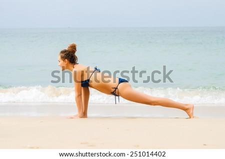 Woman doing yoga exercises on the beach - stock photo