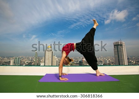 Woman doing yoga exercises on the roof of City  skyscraper - stock photo