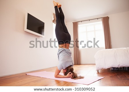 Woman Doing Yoga Fitness Exercises On Mat In Bedroom - stock photo