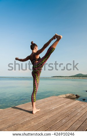 Woman doing yoga in the morning at the sea.