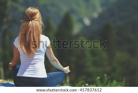 woman doing yoga meditating in the lotus position with his back to nature in the summer - stock photo