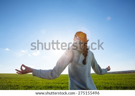 woman doing yoga on the grass field during sunset - stock photo