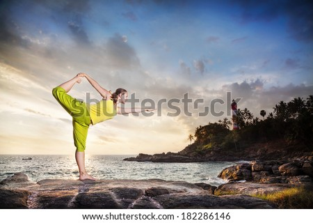 Woman doing yoga on the stone nearby ocean at lighthouse background in Kovalam, Kerala, India - stock photo