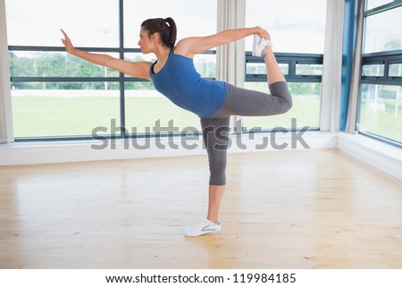 Woman doing yoga pose in fitness studio