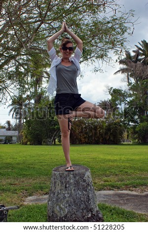 Woman doing yoga tree pose with hands above head and smiling on the stump of an old tree outside surrounded by trees and greenery - stock photo