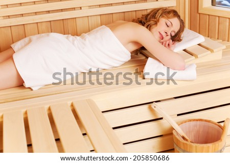 Woman dozing in a sauna lying stretched out on the wooden bench with her eyes closed in enjoyment