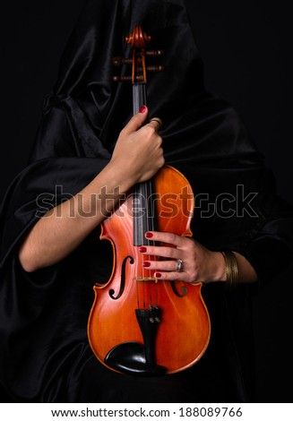 Woman draped in black holds her treasured violin musical instrument - stock photo