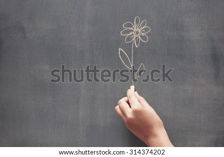 Woman drawing a flower on a blackboard - stock photo