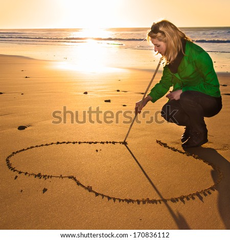Woman drawing a heart shape in the sand during the pleasant walk along the beach on a cold sunny winter day. Out off season beach leisure activities. - stock photo