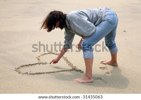 Woman draws a heart in the sand on a beach - stock photo
