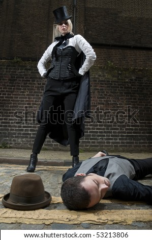 Woman dressed as Jack the Ripper on top of man lying on the ground. - stock photo