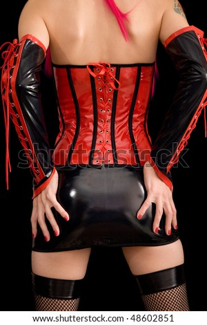 Woman dressed in dominatrix clothes, from back, isolated on black background - stock photo