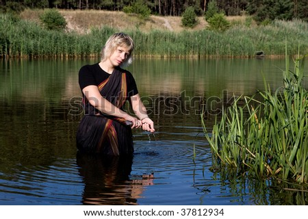 woman dressed in Indian saris washes in the river